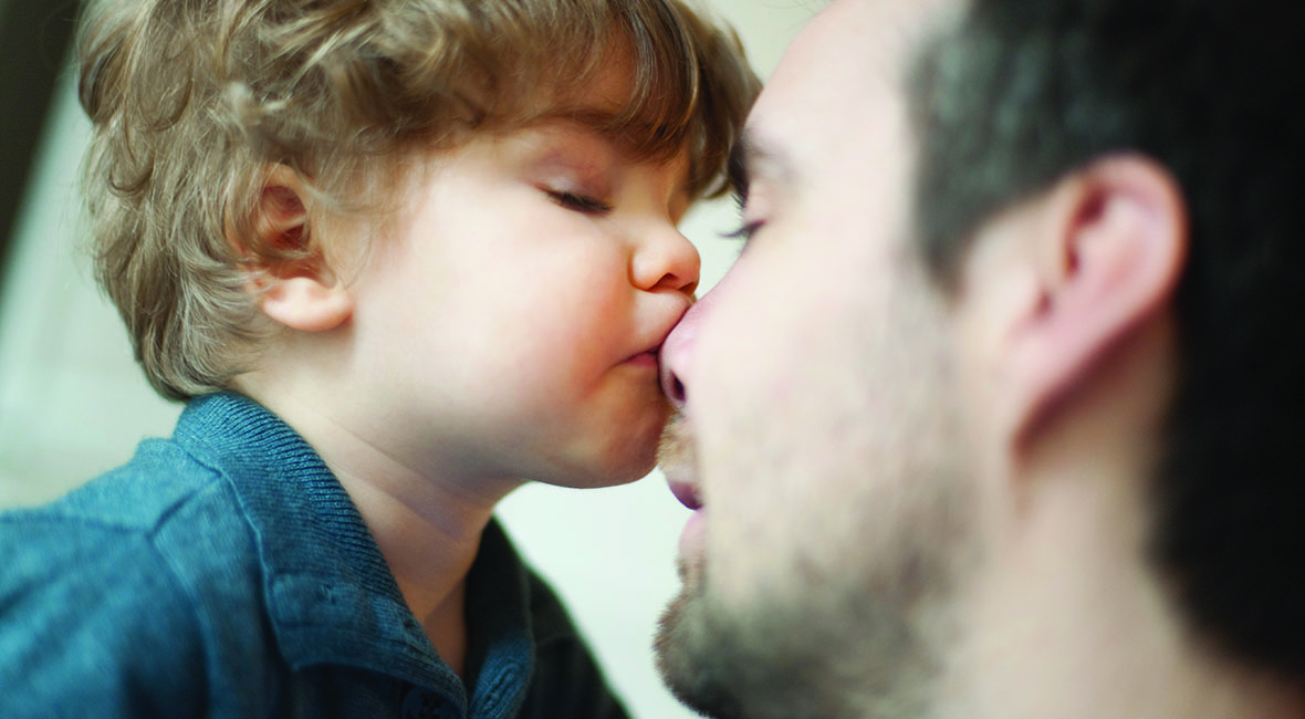 Child kissing fathers nose